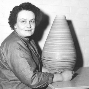 photo of woman sitting next to lined, ceramic vase