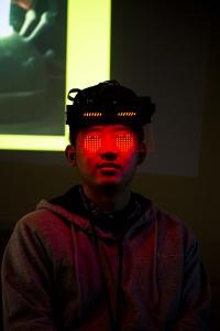 Jerry Li, figure wearing visor with red LED heart lights