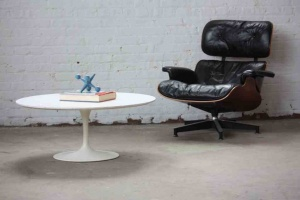 White tulip shaped table with black leather chair with headrest
