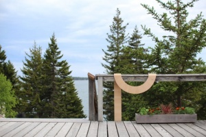 Curved wooden artwork, draped over a railing with pine trees in the distance