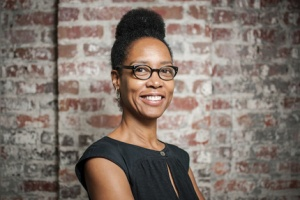 Profile photos of Artist Sonya Clark in front of brick wall