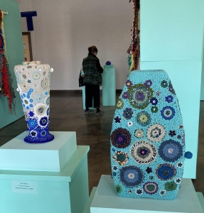 Two beaded sculptures on display pedestals in a gallery.