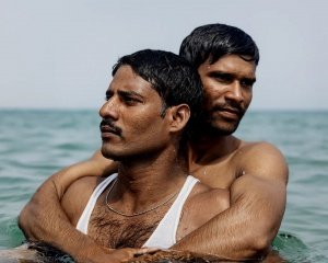 Two men swimming in ocean, one hugging the other from behind