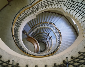 Overhead view looking down multiple levels of a large spiral staircase. The stoen staircase has gold/bronze colored handrail with decorative horizontal lines