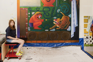 A person with long red hair sits on a red stool at the far left of a studio space. The majority of the picture shows a large painting in process hung on a wall. A partial canvas is visible in the lower right.